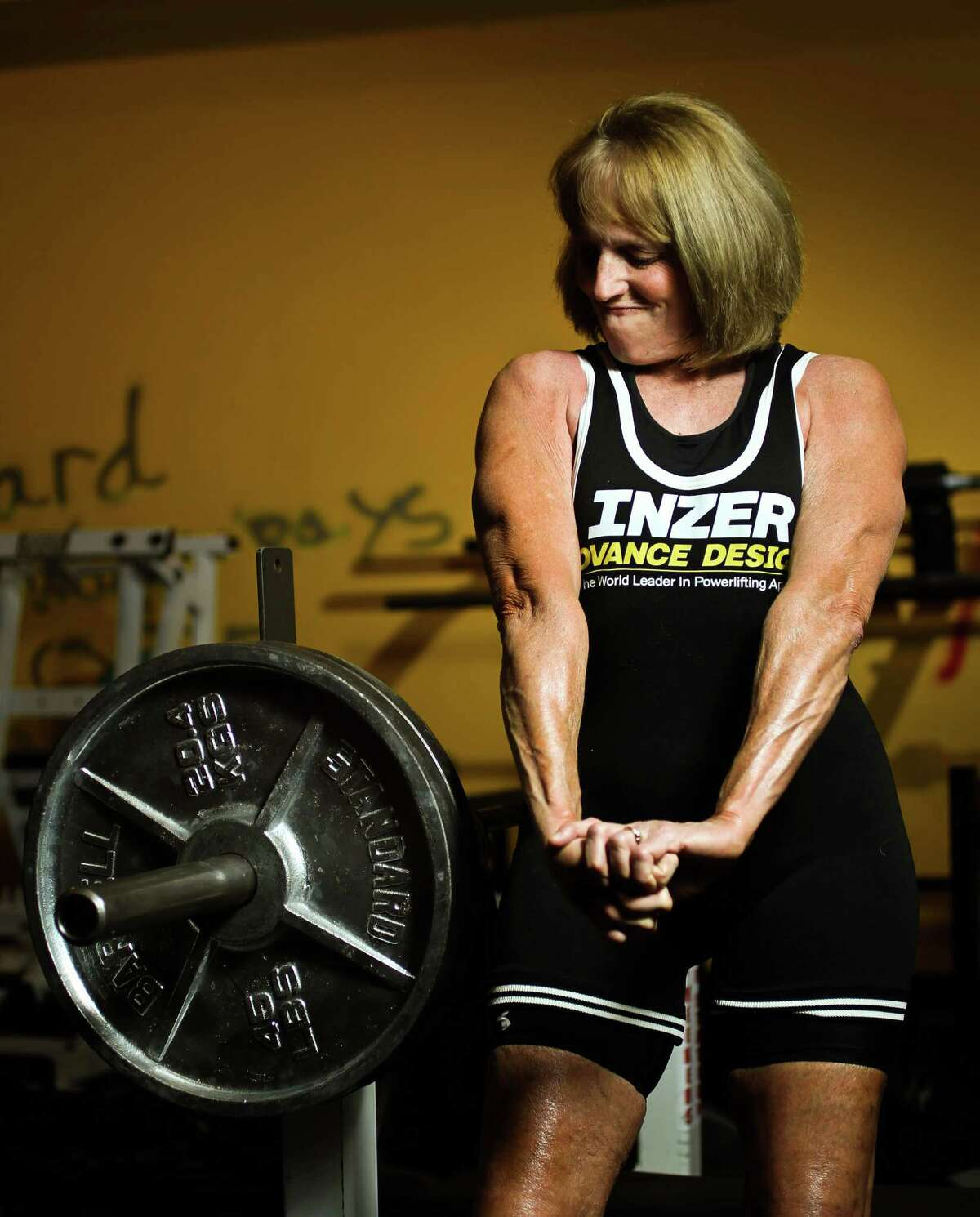 Jill Porter, of the Texas Super Team weightlifting team and world title holder, shows off her recently developed triceps, Wednesday, Jan. 9, in Monster Gym in Kingwood. Porter is planing on having a hip replaced with a new less invasive method. ( Nick de la Torre / Houston Chronicle )