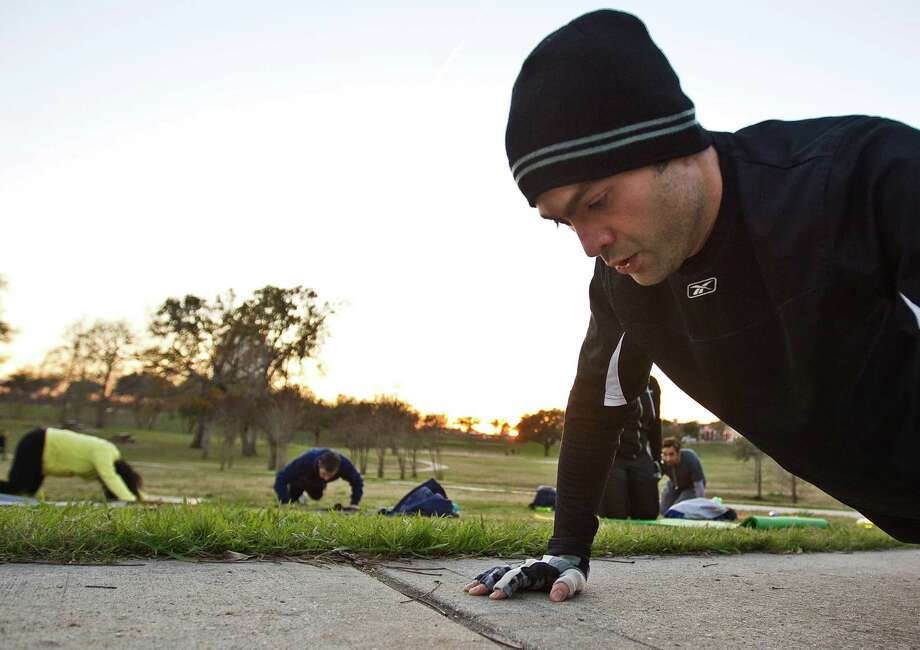Taylan Ilhan completes his second set of 30 push ups as he participates in his boot camp workout, Wednesday, Jan. 16, at Spotts Park  in Houston.( Nick de la Torre / Houston Chronicle ) Photo: Nick De La Torre, Staff / © 2013  Houston Chronicle