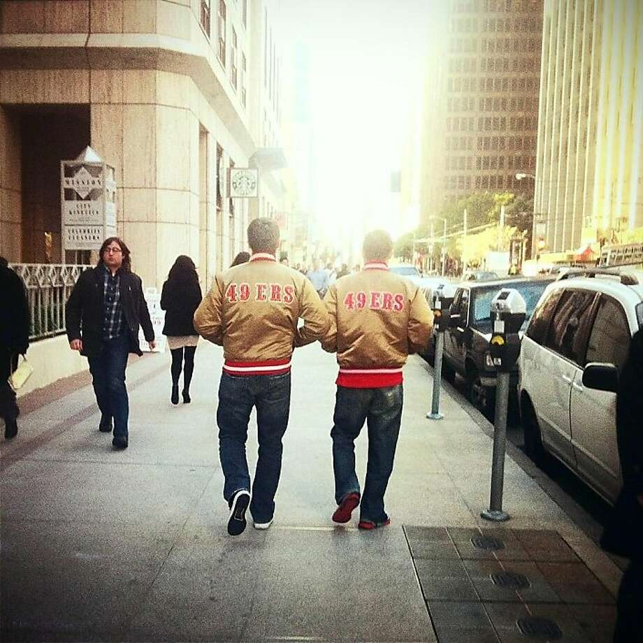 Charlie Walker and his boss walk through the Financial District of San Francisco in their gold satin 49ers jackets. Photo: Courtesy Charlie Walker