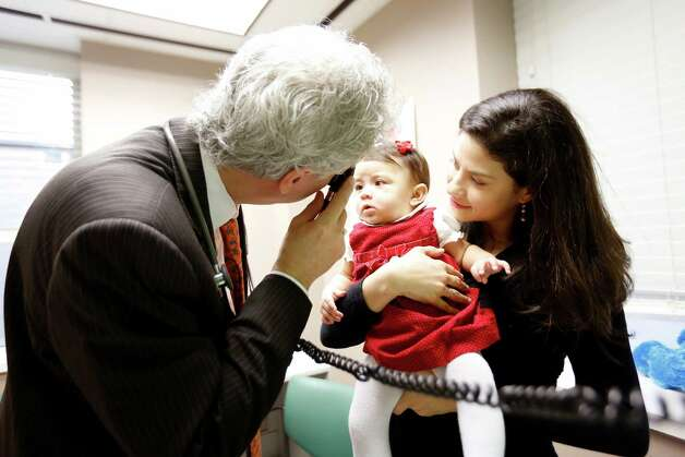 Pediatric gastroenterologist, Dr. Marc Rhoads examines patient, 7-month-old Ana Sofia Munoz, while mother, Ana Maria Orozco looks on, Friday, January 11, 2013 at the Memorial Hermann Children's Hospital in Houston, Texas. (Todd Spoth/For the Chronicle) Photo: TODD SPOTH, Photographer / Todd Spoth