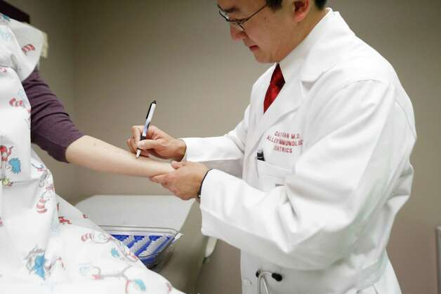 Pediatric allergist, Dat Tran, prepares a patient for an allergy test, Friday, January 11, 2013 at the Memorial Hermann Children's Hospital in Houston, Texas. (Todd Spoth/For the Chronicle) Photo: TODD SPOTH, Photographer / Todd Spoth