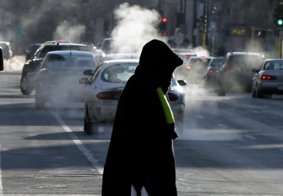 Steam from car's exhaust rises as a woman dressed for the weather crosses a street Tuesday, Jan. 22, 2013 in downtown Minneapolis where temperatures were in the double-digit, sub-zero numbers. (AP Photo/Jim Mone) Photo: Jim Mone, ASSOCIATED PRESS / AP2013
