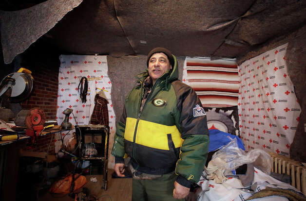 Eddie Saman shows off his home which he has insulated with blankets donated by the Red Cross, Wednesday, Jan. 23, 2013 in the borough of Staten Island in New York. The house was badly damaged by Superstorm Sandy and will have to be renovated. Meanwhile, because of the extreme cold weather, Saman has been spending the night in a tent nearby operated by the volunteer group Cedar Grove Community Hub.   (AP Photo/Mark Lennihan) Photo: Mark Lennihan, ASSOCIATED PRESS / AP2013