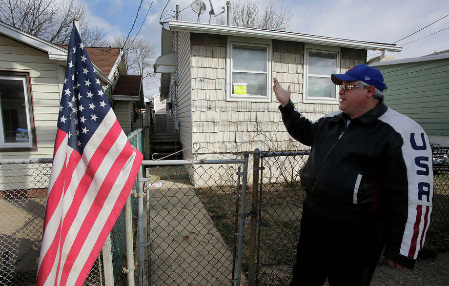 Anthony Gambino points to the house he rents, Wednesday, Jan. 23, 2013 in the borough of Staten Island in New York. The house was badly damaged by Superstorm Sandy and renovations are not yet complete. Meanwhile, because of the extreme cold weather, Gambino has been spending the night in a tent nearby operated by the volunteer group Cedar Grove Community Hub.  (AP Photo/Mark Lennihan) Photo: Mark Lennihan, ASSOCIATED PRESS / AP2013