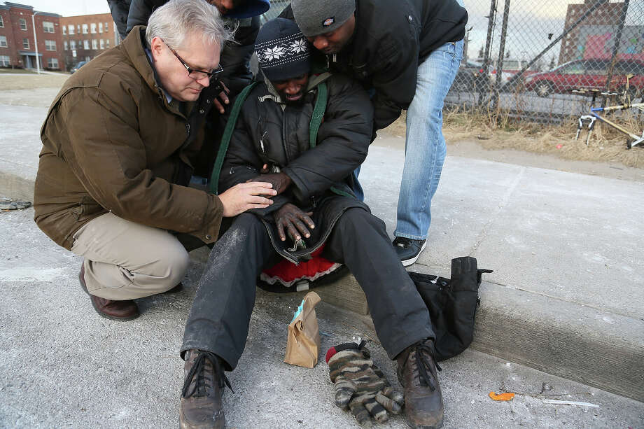 Neighborhood Service Organization Nurse Practitioner Dean Carpenter, left, and NSO Supervisor of Consumers Terrance Foster, right, come to the aid of Angelo Foster, 51, whose hands were headed into stage one frostbite outside of the NSO where Foster often stays Tuesday Jan. 22, 2013 in Detroit.  The freezing cold temperatures are having a huge impact on the homeless community. MANDI WRIGHT/Detroit Free Press  (AP Photo/Detroit Free Press,Mandi Wright)  DETROIT NEWS OUT;  NO SALES Photo: MANDI WRIGHT, ASSOCIATED PRESS / AP2013
