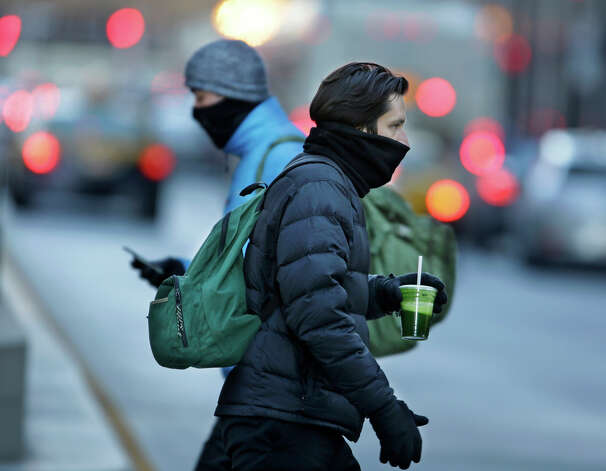 Commuters bundle up against extreme cold conditions Tuesday, Jan. 22, 2013, in Chicago. Temperatures in the area were hovering around zero with sub-zero wind chill reading hitting 10 below. Forecasters say waves of frigid Arctic air began moving over the region Saturday night Jan. 19, 2013. (AP Photo/M. Spencer Green) Photo: M. Spencer Green, ASSOCIATED PRESS / AP2013