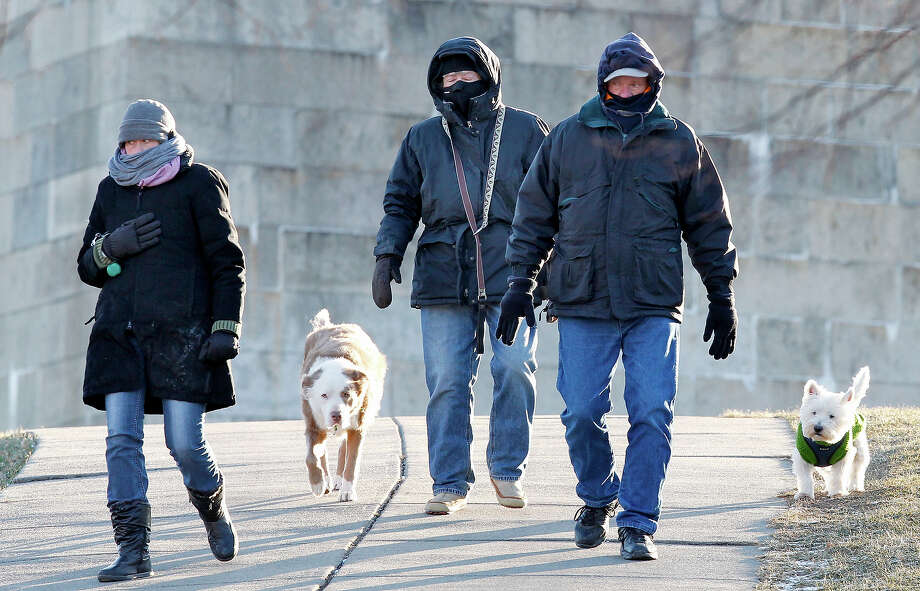 South Boston residents who did not wish to be identified walk their dogs at Castle Island in Boston, Wednesday, Jan. 23, 2013.  The National Weather Service says it's not expected to get above 17 degrees in Boston, with the wind chill making it feel five below. (AP Photo/Michael Dwyer) Photo: Michael Dwyer, ASSOCIATED PRESS / AP2013