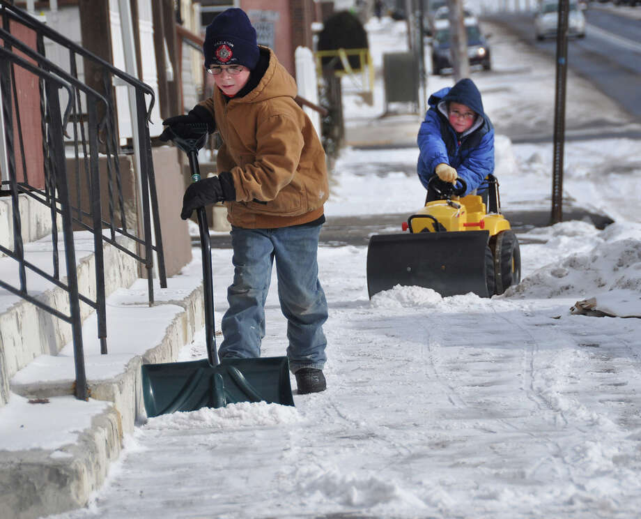 Despite single digit temperatures, Jordan Klein, 10, uses a shovel to clear the snow from the sidewalk near his grandmotherís home in Hazleton, Pa., Tuesday Jan. 22, 2013 as his eight-year-old brother Jayden works in tandem by pushing his toy tractor.   The two boys took advantage of a day off of school on Tuesday and spent some time outdoors.(AP Photo/Hazleton Standard-Speaker Ellen F. O'Connell) Photo: Ellen F. O'Connell, ASSOCIATED PRESS / AP2013