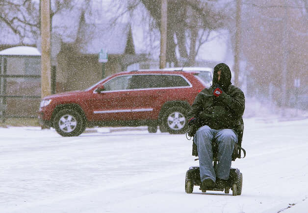 A bundled-up James Jennings makes his way along a street in Hartford, Ill., on a cold and snow Tuesday, Jan. 22, 2013. Jennings had just dropped off his grandson at school and was on his way home on his motorized scooter. (AP Photo/The Telegraph, John Badman) BELLEVILLE OUT  ST. LOUIS OUT Photo: John Badman, ASSOCIATED PRESS / OUT ILBND and STLPOSTD2013