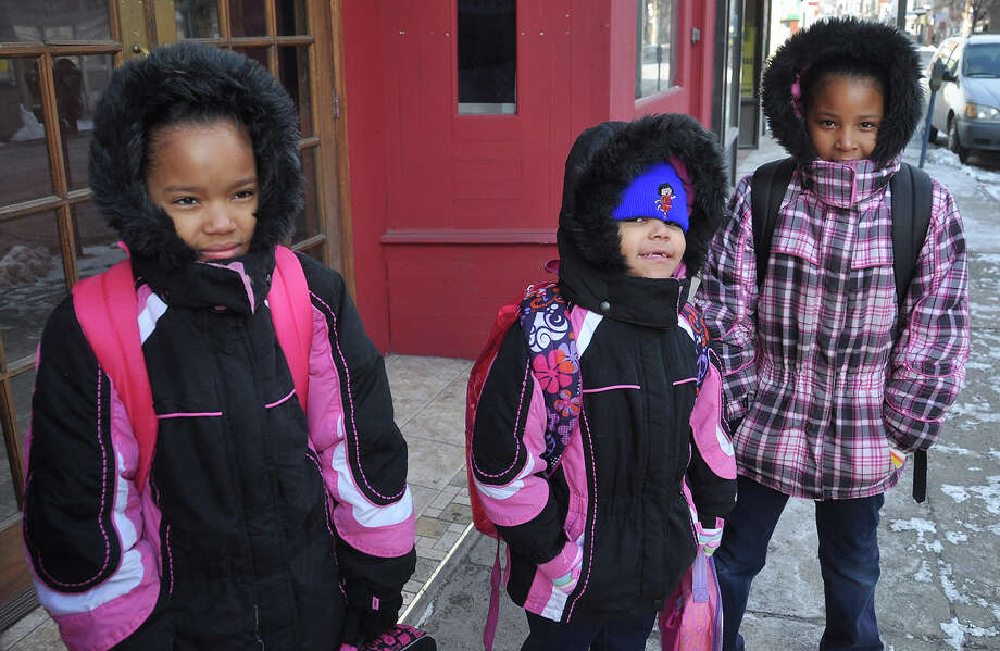With temperatures rising to 9 degrees, nine-year-old Ashley Luciano,  left, and her sisters Breanna Miera, 5, center and Jennifer Luciano, 8, are all bundled up as they wait on North Wyoming Street in Hazleton, Pa., for a school bus to take them to Heights-Terrace Elementary/Middle School on Wednesday, January 23, 2013.  (AP Photo/Hazleton Standard-Speaker Ellen F. O'Connell) Photo: Ellen F. O'Connell, ASSOCIATED PRESS / AP2013