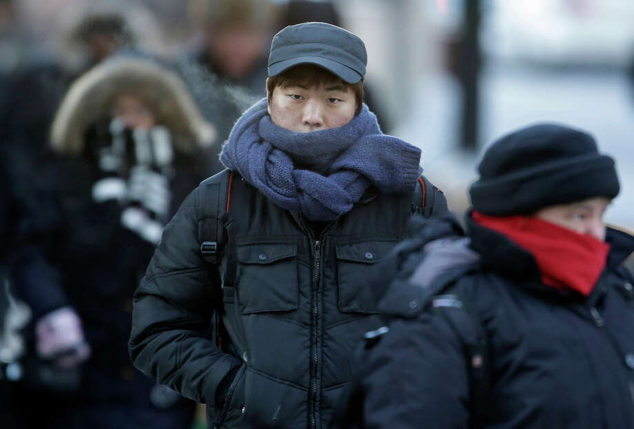 Commuters bundle up against extreme cold conditions Tuesday, Jan. 22, 2013, in Chicago. Temperatures in the area were hovering around zero with sub-zero wind chill reading hitting 10 below. Forecasters say waves of frigid Arctic air began moving over the region Saturday night Jan. 19, 2013. Temperatures are expected to rebound Wednesday Jan. 23, 2013. (AP Photo/M. Spencer Green) Photo: M. Spencer Green, ASSOCIATED PRESS / AP2013