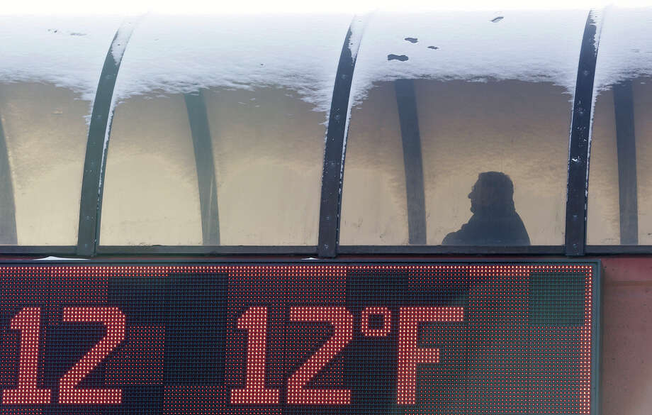 A thermometer shows the temperature as a man walks to a parking garage during the cold winter weather in Buffalo, N.Y., Tuesday, Jan. 22, 2013. (AP Photo/David Duprey) Photo: David Duprey, ASSOCIATED PRESS / AP2013