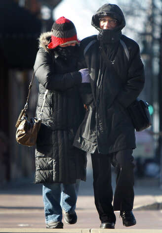 Father and daughter Emmy, left, and Shiyuam Yu Look brave the cold as they walk to a restaurant on Tuesday Jan. 22, 2013, in Appleton, Wis.   The upper Midwest is in it's a third straight day of bitter cold temperatures.  (AP Photo/The Post-Crescent,William Glasheen ) NO SALES Photo: William Glasheen, ASSOCIATED PRESS / Wm. Glasheen/The Post-Crescent2013