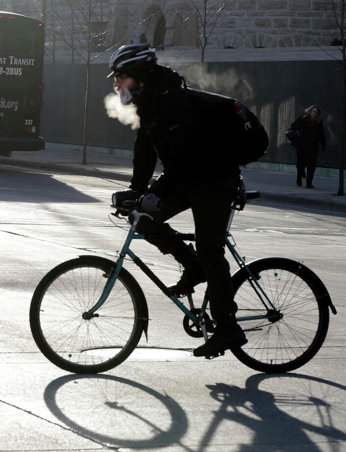 The breath of a bicyclist turns to steam and his beard frosts over as he bikes down the Nicollet Mall Tuesday, Jan. 22, 2013 in downtown Minneapolis where temperatures were in the double-digit, sub-zero numbers. (AP Photo/Jim Mone) Photo: Jim Mone, ASSOCIATED PRESS / AP2013
