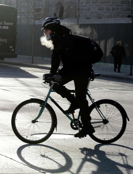 The breath of a bicyclist turns to steam and his beard frosts over as he bikes down the Nicollet Mal