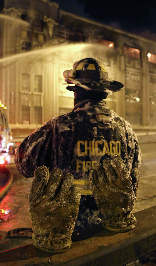 The frozen ice covered pair of gloves belonging to a Chicago firefighter stand on a railing behind him in single digit temperatures during a five-alarm blaze in a warehouse on the city's South Side, Bridgeport neighborhood rages Wednesday, Jan. 23, 2013, in Chicago. (AP Photo/Charles Rex Arbogast) Photo: Charles Rex Arbogast, ASSOCIATED PRESS / The Associated Press2013