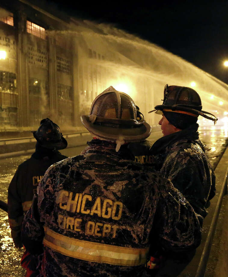 Chicago firefighters are covered in ice from single digit temperatures as they take a break from a five-alarm blaze in a warehouse on the city's South Side, Bridgeport neighborhood Wednesday, Jan. 23, 2013, in Chicago. (AP Photo/Charles Rex Arbogast) Photo: Charles Rex Arbogast, ASSOCIATED PRESS / The Associated Press2013