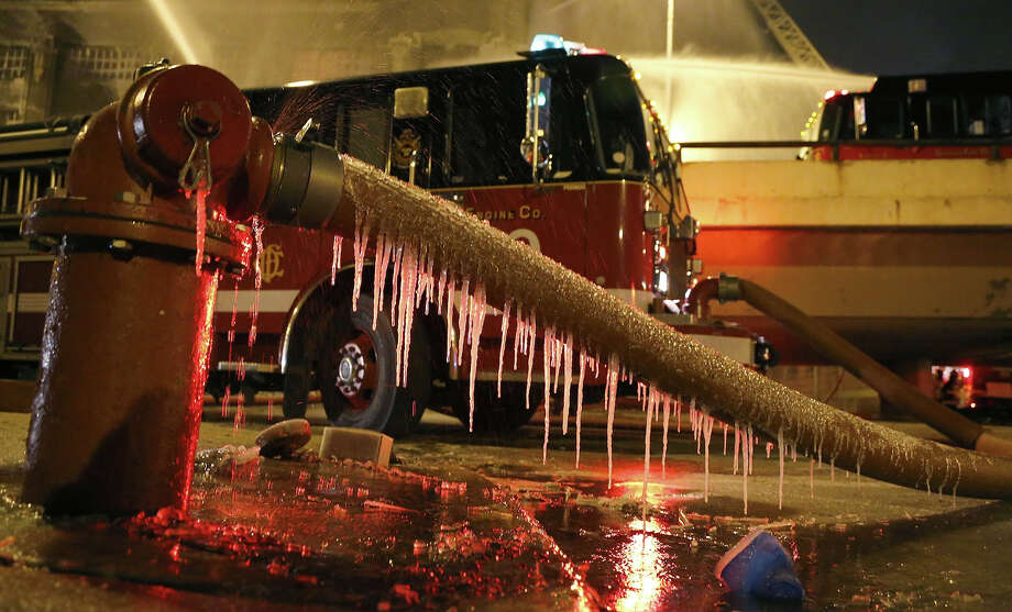 Icicles form on a fire hose from single digit temperatures as Chicago firefighters battle a five-alarm blaze in a warehouse on the city's South Side, Bridgeport neighborhood Wednesday, Jan. 23, 2013, in Chicago. (AP Photo/Charles Rex Arbogast) Photo: Charles Rex Arbogast, ASSOCIATED PRESS / AP2013