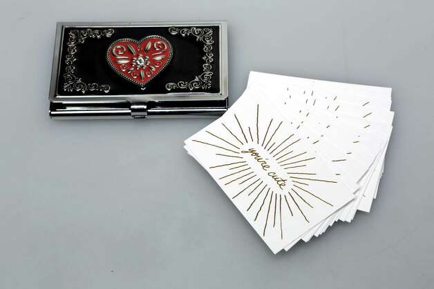 "Black-lacquered heart business card holder, $24 from On Main/Off Main teamed with ""You're cute"" gold embossed cards that are blank on the other side for notes and other love-connection info, $10 from Sloan/Hall. Photo: Helen L. Montoya, San Antonio Express-News / ©2013 San Antonio Express-News"