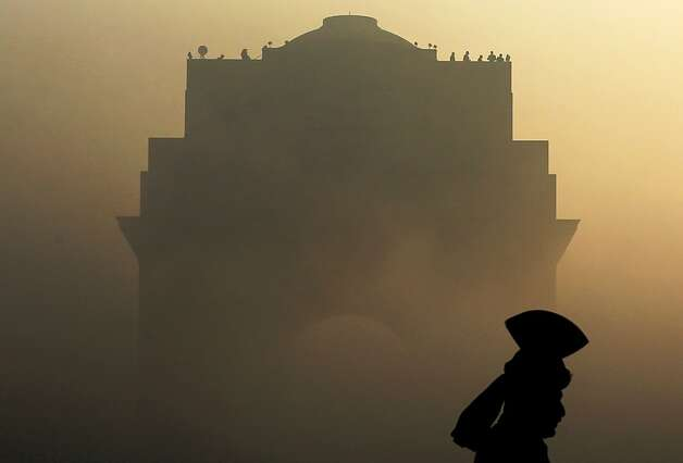Sentry at the gate: An Indian Army soldier in ceremonial dress stands guard at the fog-shrouded India Gate monument in New Delhi. India will celebrate Republic Day on Saturday. Photo: Kevin Frayer, Associated Press