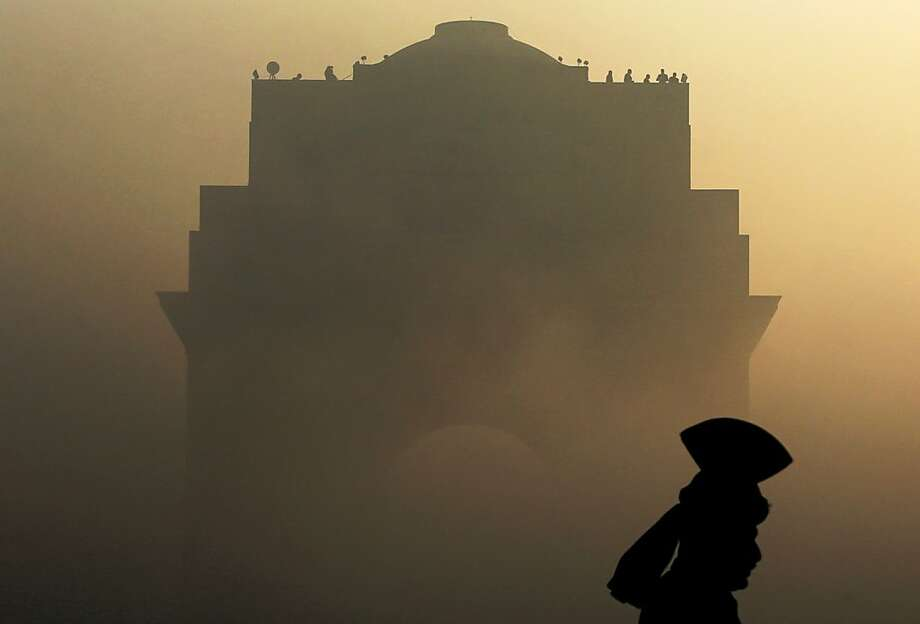 An Indian Army soldier in ceremonial dress stands guard as the India Gate monument is shrouded in heavy fog prior to a dress rehearsal for the annual Republic Day parade in New Delhi, India, Wednesday, Jan. 23, 2013. India celebrates Republic Day annually on Jan. 26. Photo: Kevin Frayer, Associated Press
