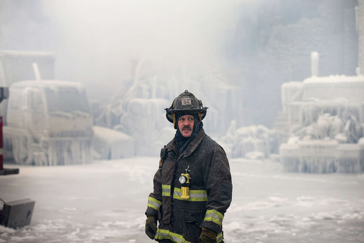 CHICAGO, IL - JANUARY 23: A firefighter helps to extinguish a massive blaze at a vacant warehouse on January 23, 2013 in Chicago, Illinois. More than 200 firefighters battled a five-alarm fire as temperatures were in the single digits.