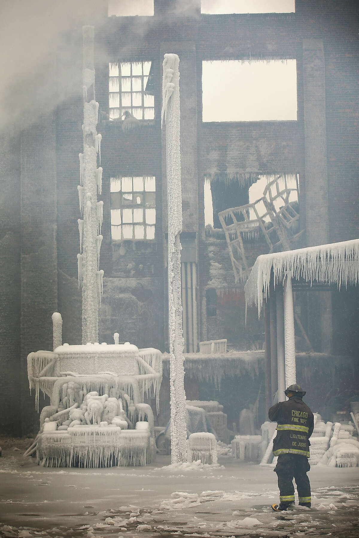 CHICAGO, IL - JANUARY 23: Firefighters help to extinguish a massive blaze at a vacant warehouse on January 23, 2013 in Chicago, Illinois. More than 200 firefighters battled a five-alarm fire as temperatures were in the single digits.