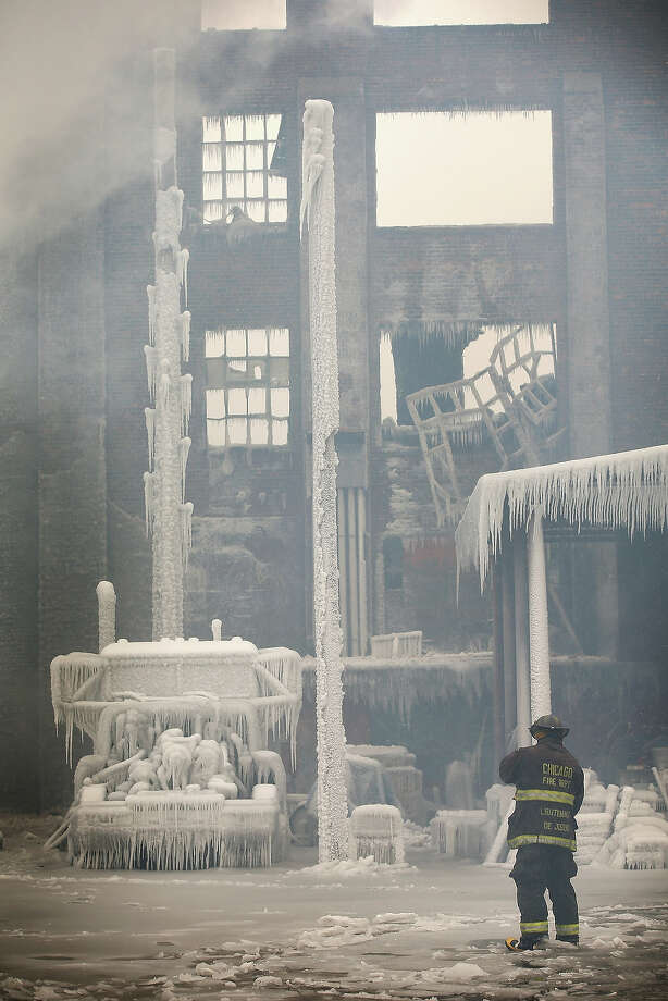 CHICAGO, IL - JANUARY 23: Firefighters help to extinguish a massive blaze at a vacant warehouse on January 23, 2013 in Chicago, Illinois. More than 200 firefighters battled a five-alarm fire as temperatures were in the single digits. Photo: Scott Olson, Getty Images / 2013 Getty Images