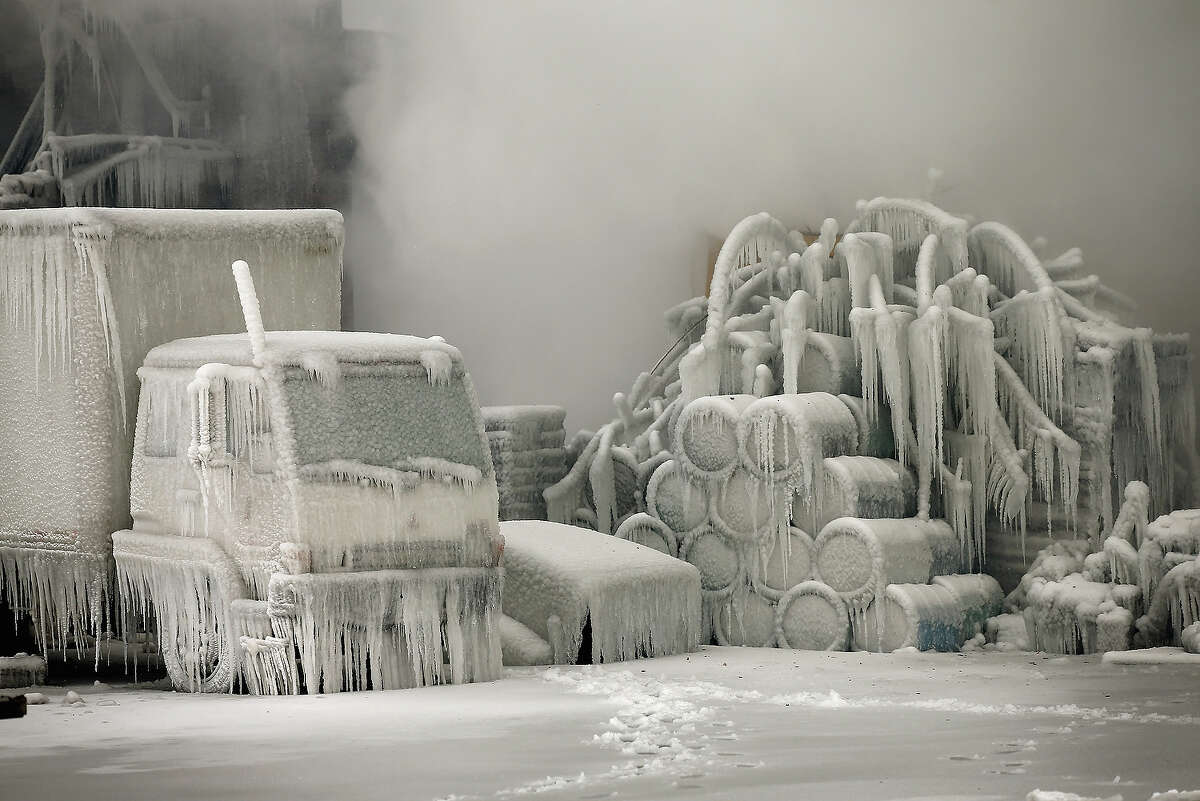 CHICAGO, IL - JANUARY 23: A truck is covered in ice as firefighters help to extinguish a massive blaze at a vacant warehouse on January 23, 2013 in Chicago, Illinois. More than 200 firefighters battled a five-alarm fire as temperatures were in the single digits.