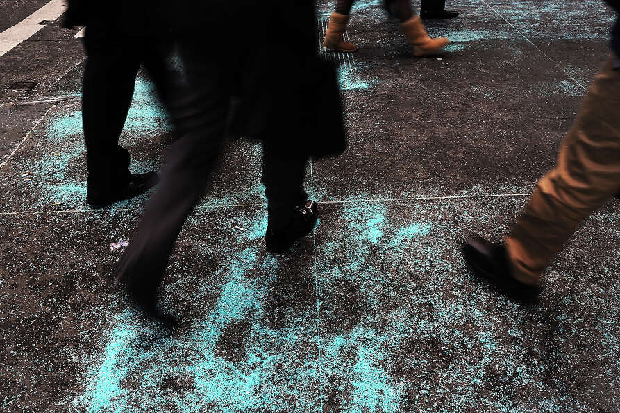 NEW YORK, NY - JANUARY 22:  Pedestrians walk over blue salt on the sidewalk after a light snow fall