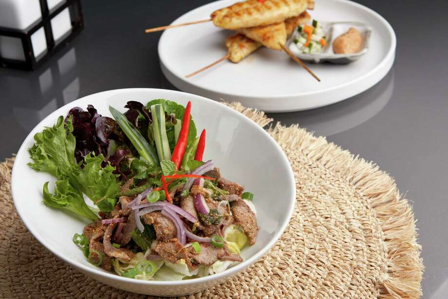 This Asian-style salad with steak, greens and vegetables is one variation on a popular dish. chicken satay barbecued chicken on skewers appetizers in the background. / TheSupe87 - Fotolia