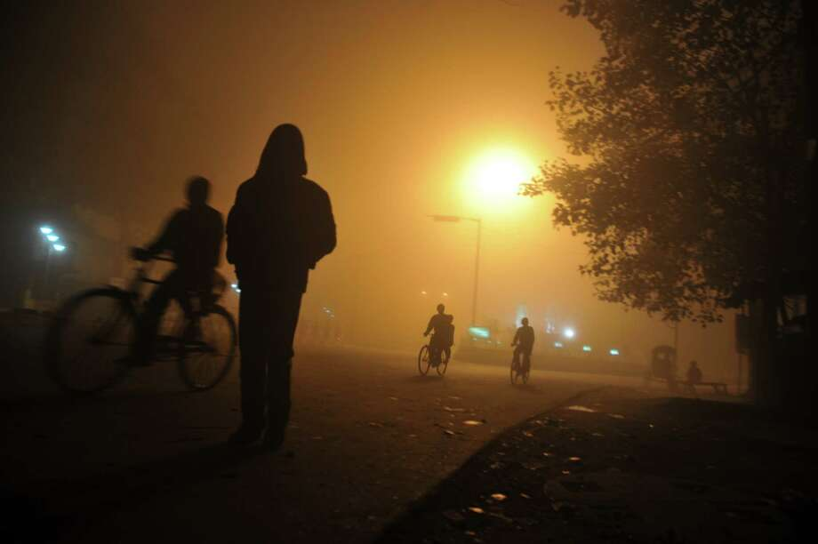 Indian commuters make their way through thick fog along a road during a foggy night in Siliguri on January 24, 2013. Photo: DIPTENDU DUTTA, AFP/Getty Images / AFP