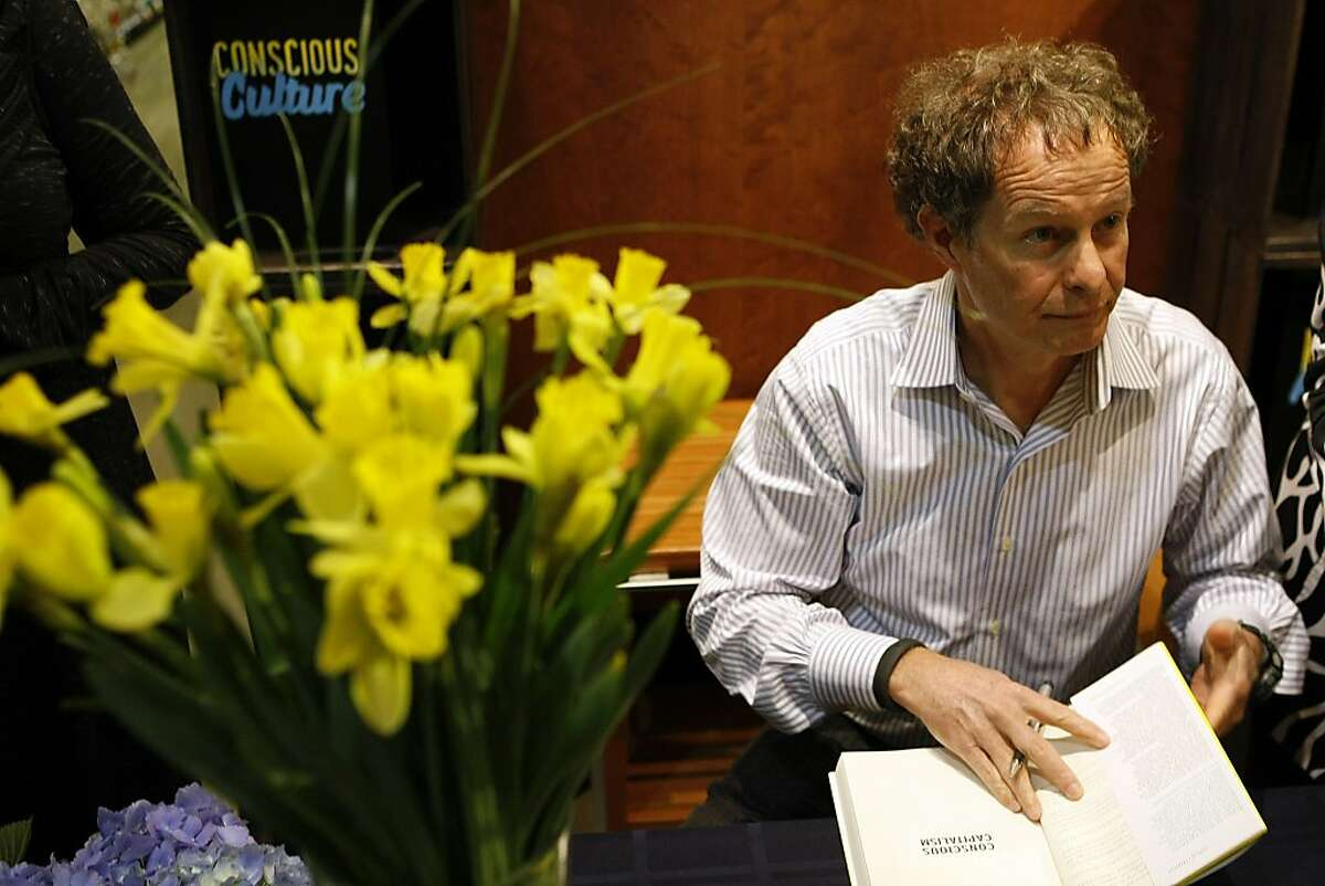 John Mackey looks up to speak to a purchaser of his new book ,