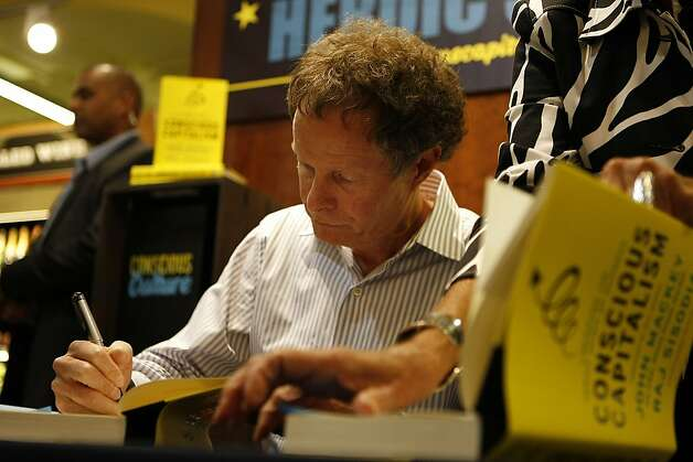"John Mackey signs a copy of his book, ""Conscious Capitalism: Liberating the Heroic Spirit of Business"" during a book signing at the Whole Foods in Potrero on January 22, 2013 in San Francisco, Calif. Mackey is both co-founder and co-CEO of the Whole Foods supermarket chain. Photo: Sean Havey, The Chronicle"