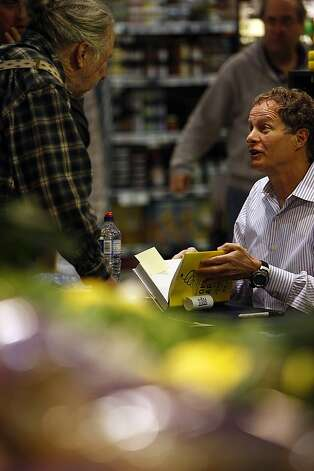 Patrick Gorman, of San Francisco, talks to John Mackey as he signs his new book, Conscious Capitalism at the Whole Foods in Potrero on January 22, 2013 in San Francisco, Calif. Mackey is both co-founder and co-CEO of the Whole Foods supermarket chain. Photo: Sean Havey, The Chronicle