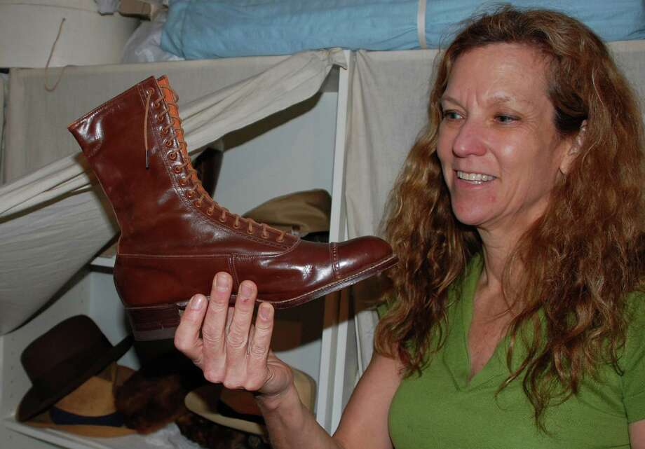 Elizabeth DeVoll, education director at the Westport Historical Society, inspects historic footwear in the institution's collection. Photo: Jarret Liotta / Westport News contributed