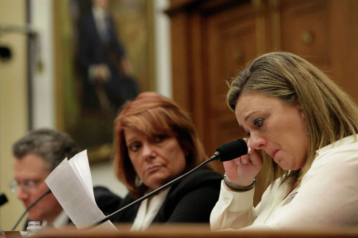 WASHINGTON, DC - January 23 - Technical Sergeant Jennifer Norris, USAF, (ret) wipes a tear as she testifies at a review of sexual misconduct by basic training instructors at Lackland Air Force Base by House Armed Services Committee, 2118 Rayburn Building. At left are witnesses David Lisak, PH.D., forensic Consultant and Chief Master Sergeant Cindy McNally, USAF(ret)