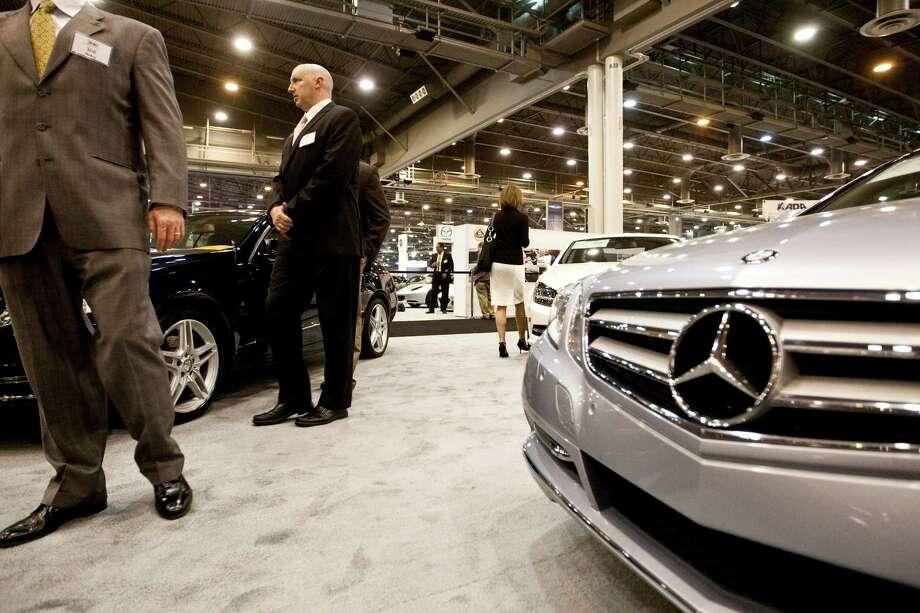 Frank Grazier, center, of McAllen and Service Group auto vendor, walks past a Mercedes Benz E 350 Cabriolet during the Houston Auto Show Preview Party. Photo: Nick De La Torre, Staff / © 2013  Houston Chronicle