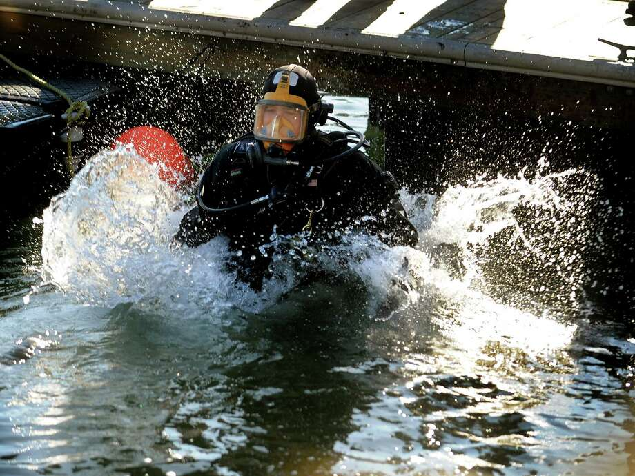 Officer Albert Palatiello leaps into the waters of Bridgeport Harbor during a training exercise with the Bridgeport Police Dive Team on Wednesday, January, 23, 2013. The water was about 40 degrees, warm compared to the air temperatures which hovered in the single digits. Lt. Brian Fitzgerald said that dive equipment needed to get into the water quickly, because with the extreme cold it can freeze up and become inoperable. Photo: Brian A. Pounds