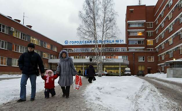 People walk at City Hospital No. 31 in St. Petersburg, Russia, Wednesday, Jan. 23, 2013. Russian officials on Wednesday backed off on a plan to shut a clinic specialized in treating children with cancer in order to turn it into a medical center for the nation's top judges, marking a rare occasion when authorities seemed to bow to public pressure. The authorities intention to turn City Hospital No. 31 into a clinic that would exclusively serve judges of Russia's top courts, which are being relocated to St.Petersburg from Moscow, has caused a strong public dismay. (AP Photo/Dmitry Lovetsky) Photo: Dmitry Lovetsky, Associated Press