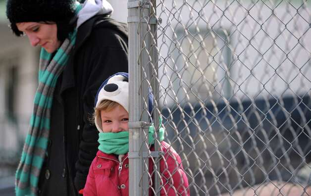 Five-year-old Lily Messer is all bundled up as she waits for her school bus with mom Angela Maiorano Wednesday, Jan. 23, 2013 in Shelton, Conn. Photo: Autumn Driscoll / Connecticut Post