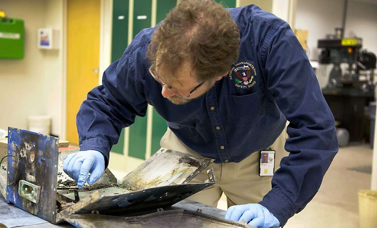 In this image released by the National Transportation Safety Board, NTSB Materials Engineer Matt Fox examines the casing from the battery involved in the Japan Airlines Boeing 787 fire in a plane that had already landed in Boston at NTSB headquarters in Washington, Wednesday, Jan. 23, 2013. (AP Photo/NTSB)