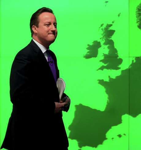 """Britain's Prime Minister David Cameron walks past a map of Europe on a screen as he walks away after making a speech on holding a referendum on staying in the European Union in London, Wednesday, Jan. 23, 2013. Cameron said Wednesday he will offer British citizens a vote on whether to leave the European Union if his party wins the next election, a move which could trigger alarm among fellow member states. He acknowledged that public disillusionment with the EU is """"at an all-time high,"""" using a long-awaited speech in central London to say that the terms of Britain's membership in the bloc should be revised and the country's citizens should have a say. (AP Photo/Matt Dunham) Photo: Matt Dunham, STF / AP"""