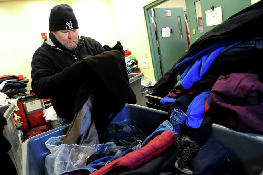 Paul Bailey, employee at Blessingdale's, sorts through about 100 donated coats on Wednesday, Jan. 23, 2013, at Capital City Rescue Mission in Albany, N.Y. Homeless and Travelers Aid Services will donate about 500 coats total to the shelter. Best Cleaners will clean the coats before they're given away. (Cindy Schultz / Times Union) Photo: Cindy Schultz / 10020878A