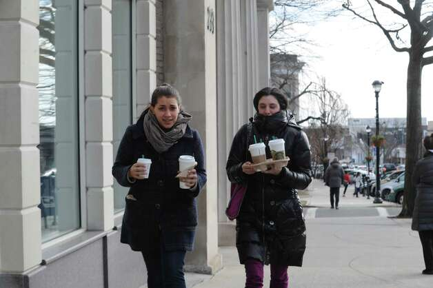 Katie Khalifa,22, left, of Greenwich, and Jaclyn Roth, 22 of Scarsdale, N.Y., brings Starbucks coffee to friends on Greenwich Avenue, Conn., Wednesday, Jan. 23, 2013.   Greenwich weather is cold, temperature of 18 F, with mostly cloudy with chance of snow. Photo: Helen Neafsey / Greenwich Time