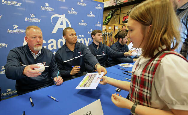 Derek Holland works on a jersey as Texas Rangers players and representatives sign autographs at the Academy Sports and Outdoors store at 1604 and NW MIlitary on January 23, 2013. Photo: Tom Reel / San Antonio Express-News / �2012 San Antono Express-News