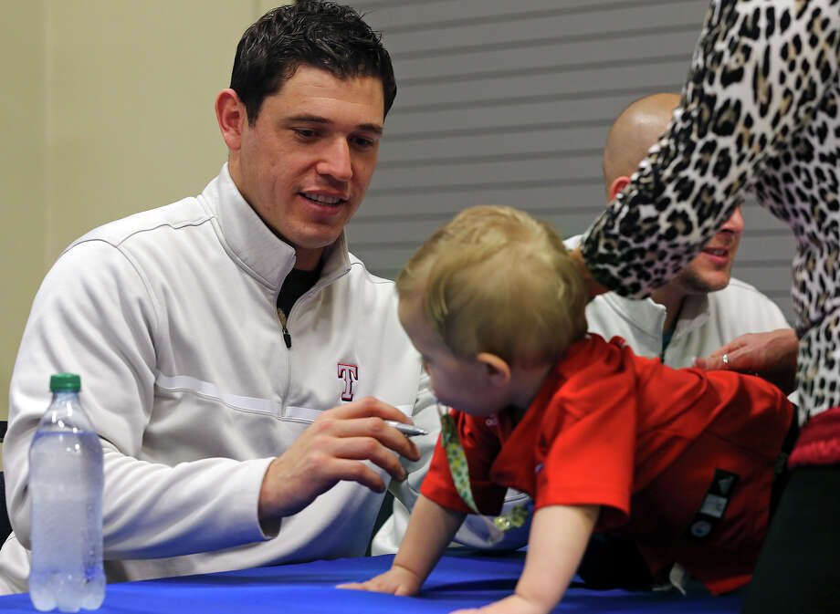 Rangers second baseman Ian Kinsler is asked to sign the shirt of one of his youngest fans at a local Academy Sports and Outdoors store Wednesday. Photo: Tom Reel, San Antonio Express-News / ©2012 San Antono Express-News