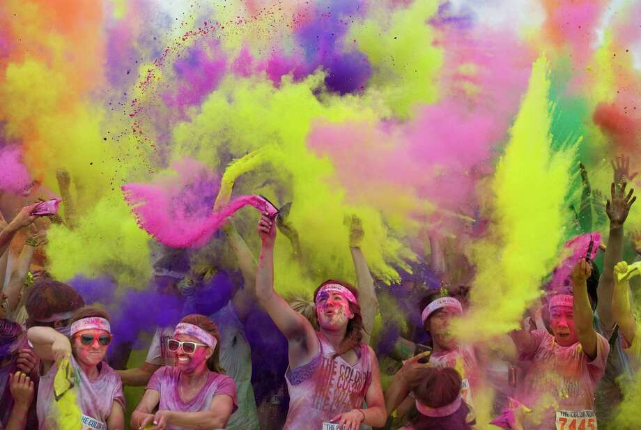 Color Run participants are doused in colors at the finish of an event last year in Irvine, Calif. Participants begin the run in white shirts, and each kilometer is associated with a designated color doused on them. Photo: Mindy Schauer, MBO / THE ORANGE COUNTY REGISTER