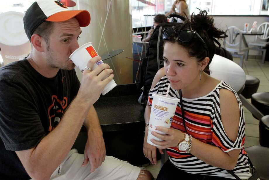 FILE - In this Sept. 13, 2012 photo, Luke Husemann, and Christina Nunez, of Baltimore, sip on extra-large soft drinks at a McDonald's restaurant in New York. The city defended its groundbreaking size limit on sugary drinks Wednesday, Jan. 23, 2013, as an imperfect but meaningful rein on obesity, while critics said it would hurt small and minority-owned businesses while doing little to help health. (AP Photo/Kathy Willens, File) Photo: Kathy Willens