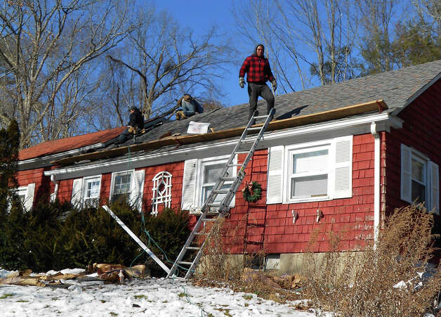 Mark Edwards and his crew work to replace the roof on Sheila Maher's house. Photo: Contributed Photo / The News-Times Contributed